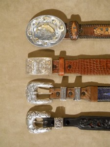 "The same four belts with their buckles. Top: a trophy buckle. 2: a narrower trophy buckle. 3: a 1"" buckle with TWO loops - note the snaps. Bottom: a 3/4"" buckle with ONE loop."